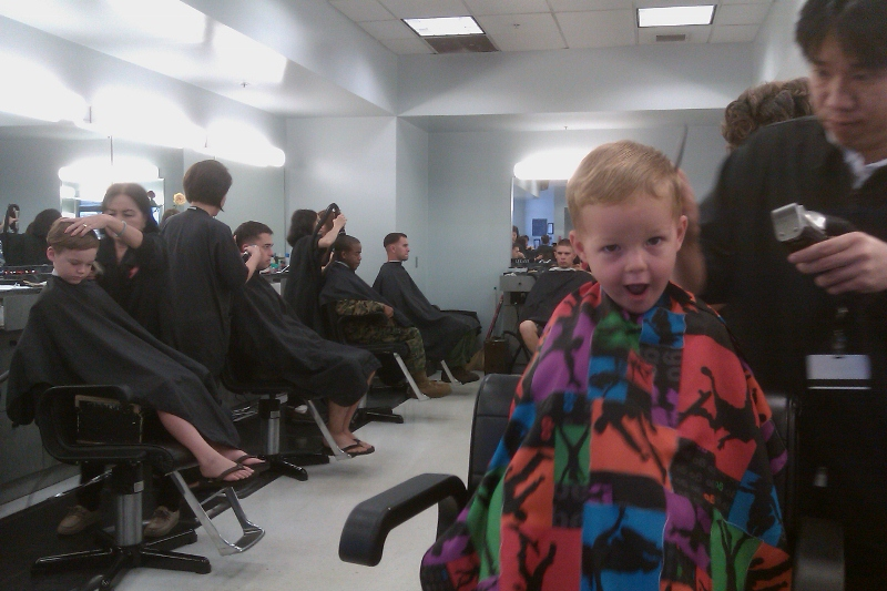 "Getting dual haircuts on Monday. Ben's faces are just so funny. He often does this one when he is uncertain. He says he's a ""BIIIG sharkie!"" and shows us his teeth - I guess. That's what we surmise he is doing."