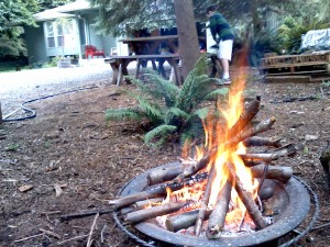 Friday fires! Sam cleaning pine needles off the picnic table for pizza with our neighbors.
