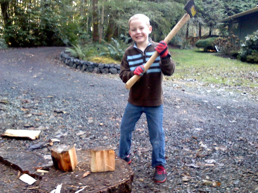 Ben doing some splitting. He is getting quite reliable, really. I had four kids out there splitting all at one time. Talk about high-intensity supervision. I was really bonking after that. Each had their own chopping block lined up along the driveway behind Ben. I had the great privilege of helping a neighbor girl chop her first piece of wood by herself.
