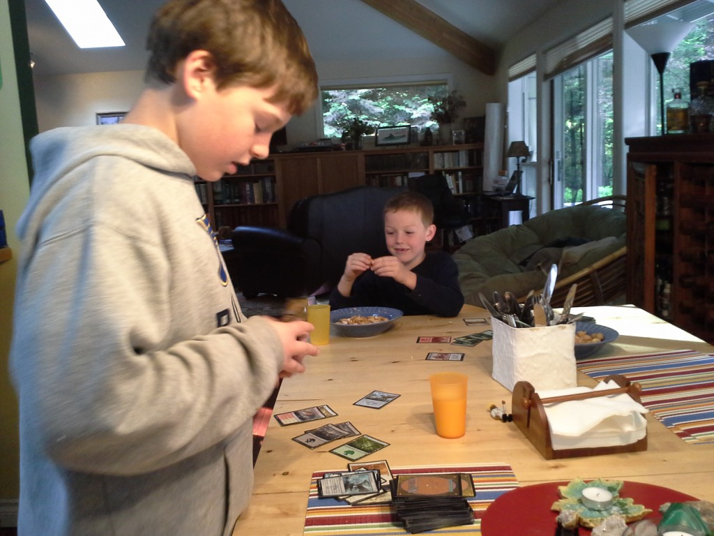 Eating peanuts and playing Magic together. They are having a relaxing afternoon after a busy week with ice hockey, science fair and other stuff...