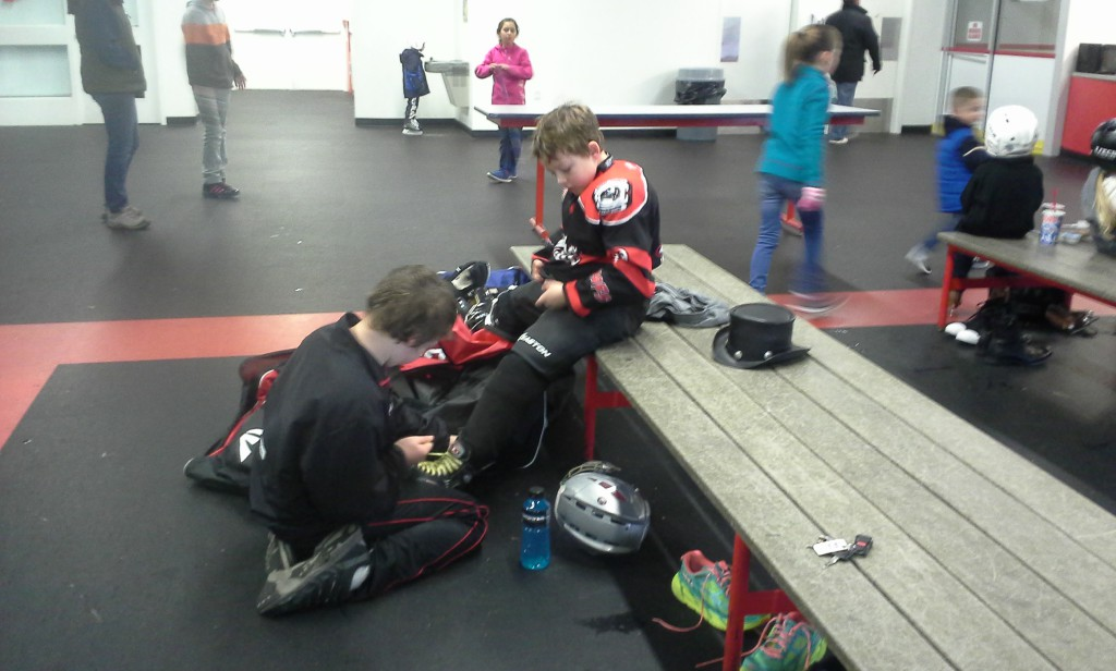 So - Sam had a game, which they won 2:1 (just barely - tough game!). Then we did open skate while waiting around for Ben's Mites practice. I spent 3 hours on the ice (I help corral kids and pucks), Sam 4 hours. Here he is tying Ben's skates. I was so tired by this time that I lost my keys 3 separate times. I finally told another mom where they were! I felt nearly drunk with tiredness, but just kept moving or I would have keeled over! Lots of fun, though.